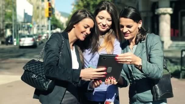 Felices empresarias atractivas con un tablet Pc en la ciudad — Vídeo de stock