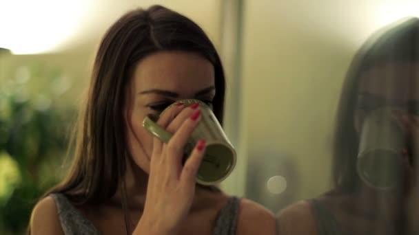 Sad, beautiful woman drinking coffee by the window at night — Vidéo