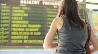 Young woman looking at screen info in the station — Stock Video