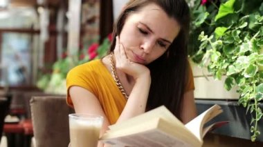 Young woman reading book, drinking juice in cafe — Stock Video