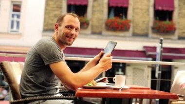 Happy man with tablet computer sitting in restaurant — Stock Video