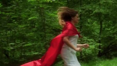 Woman in red cape running away in forest — Stok video