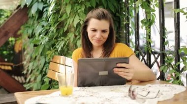 Woman watching funny movie on tablet computer in cafe — Wideo stockowe