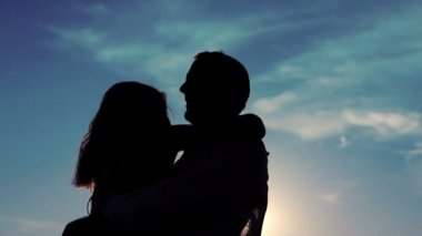 Silhouette of couple in love embracing against sun — Stok video