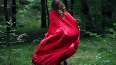 Woman in red cape run away in forest — Stockvideo