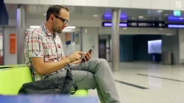 Young man listen to the music on smartphone at train terminal — Stock Video