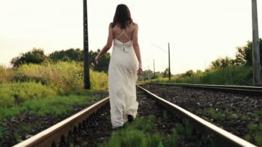 Woman in white dress walk on railroad track, — Stockvideo