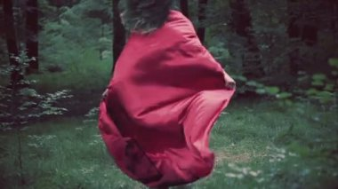 Woman in red cape running away in forest — Stockvideo