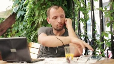 Unhappy man waiting and  check messages  in outdoor bar — Stock Video