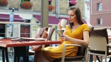 Elegant woman texting on smartphone, drinking coffee in restaurant — Stock Video