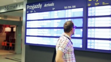 Young man looking at screen info in the station — Stock Video