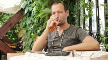 Young man raising toast with beer to camera — Vídeo Stock
