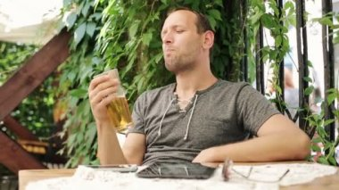 Happy man drinking cold beer in outdoor bar — Stock Video