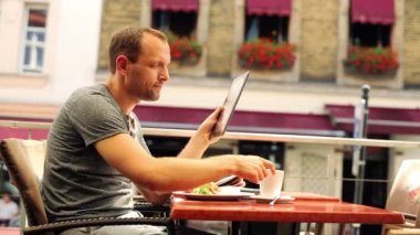 Man with tablet computer drinking coffee in restaurant — Stock Video