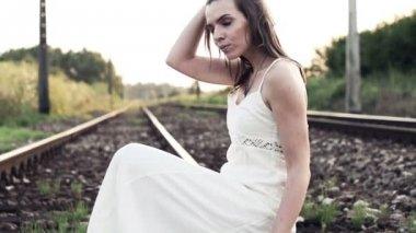 Pensive woman sitting on railroad track — Stock Video