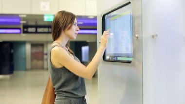 Woman checking trains timetable at modern touchscreen info kiosk — Stock Video