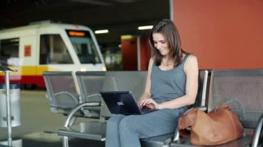 Young pretty woman with laptop computer at train station — Vídeo Stock
