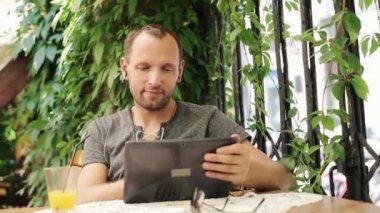 Man watching funny movie on tablet computer in restaurant — Vídeo de stock