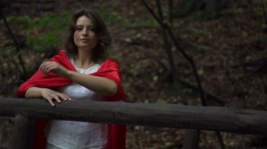 Serious beautiful mysterious woman, red riding hood in the forest — Stock Video