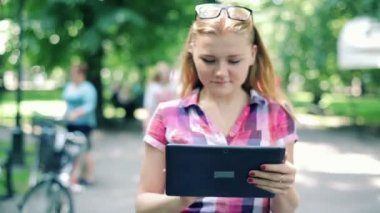 Teenage girl with tablet in park — Stock Video