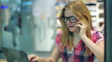 Teenager talking on cellphone  in cafe — Stock Video