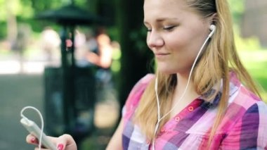 Cute teenager listen to the music on smartphone in city park — Video Stock