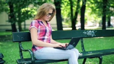 Young teenage student with modern laptop in city park — Video Stock