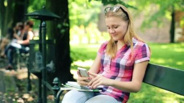Girl with smartphone on bench — Stock video