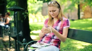 Teenage girl listen to the music on smartphone in city park — Video Stock