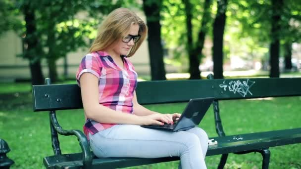 Student with modern laptop in city park — Vídeo de stock