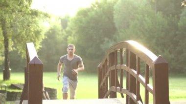 Man jogging across bridge — Stock Video