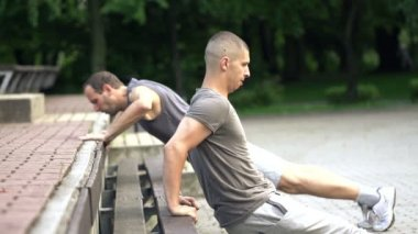Men doing push-ups in park — Stock Video