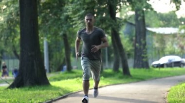 Young man jogging in city park — Stock Video