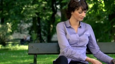 Businesswoman sitting on bench in park — Stock Video