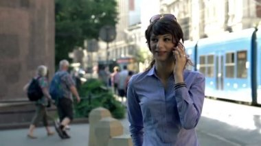 Businesswoman talking on cellphone by the street — Stock Video