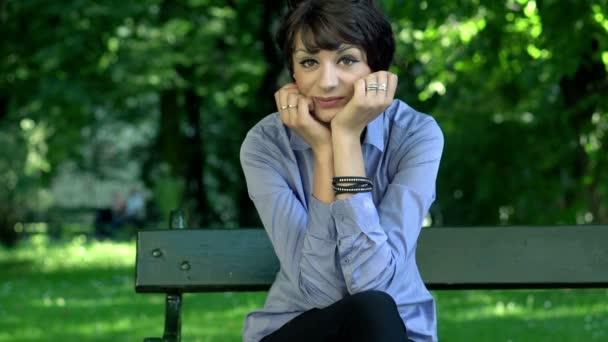 Mujer sentada en el parque de negocios — Vídeo de stock