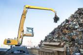 Large tracked excavator working a steel pile at a metal recycle  — Stock Photo