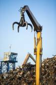 Crane claw on top of pile with scrap metal in recycling center — Stock Photo