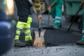 Worker operating asphalt paver machine during road construction and repairing works — Stock Photo