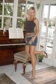 Pretty blonde posing in front of a piano — Foto de Stock