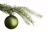 Green Christmas ball on a snowy branch — Stock Photo