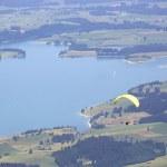 Постер, плакат: Paraglider flying over Bavarian lake