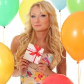 Party girl on the background balls with gift box — Stok fotoğraf