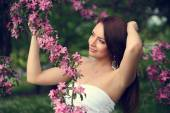 Girl in flowers of apple tree — Photo