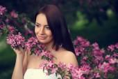 Girl in flowers of apple tree — Stock Photo