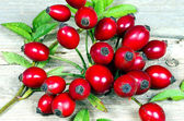 Several Rosehips with leaves on a wooden table — Stock Photo