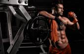 The very muscular sporty guy drinking protein in dark weight roo — Stock Photo