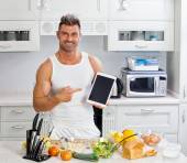 Happy handsome man cooking in kitchen at home. — Foto de Stock
