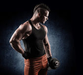 Handsome power athletic man in training pumping up muscles with — Stock Photo