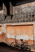 Cracked brick wall and Old rusty vintage bicycle — Stock Photo